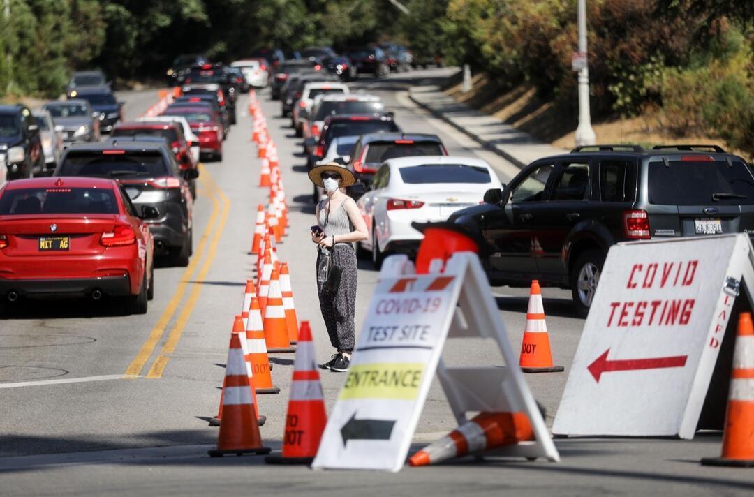 Una mujer entre autos alineados por ciudadanos que buscan hacerse la prueba de Covid-19 mientras se dirigen a un estacionamiento en el Dodger Stadium el 26 de junio de 2020 en Los Ángeles, California, Estados Unidos.