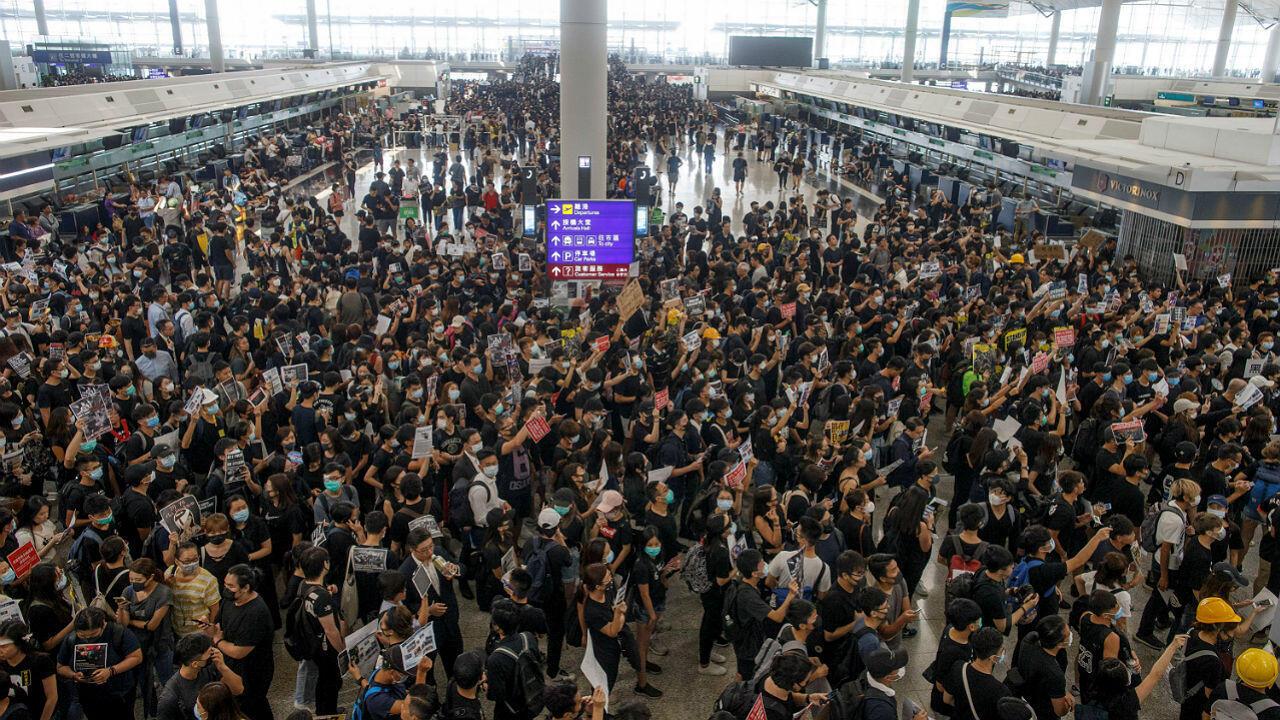 Des manifestants prodémocratie se rassemblent dans le hall des départs de l'aéroport de HongKong, le 12août2019.