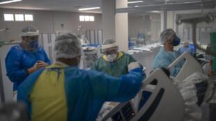 عاملون في مجال الصحة يقدمون الرعاية لمصاب بكوفيد-19 في وحدة العناية المركزة في مستشفى الدكتور ارنستو تشي غيفارا الحكومية في مدينة ماريكا في ولاية ريو دي جانيرو في البرازيل في 5 حزيران/يونيو 2020