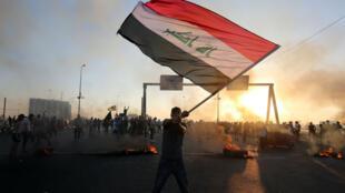 Un manifestant irakien brandit le drapeau national lors d'une manifestation contre la corruption de l'État, les services publics défaillants et le chômage, à Bagdad, le 5 octobre 2019.