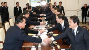 Delegaciones diplomáticas de Corea del Sur y Corea del Norte se dan la mano en una reunión en la zona desmilitarizada de Panmunjom que separa los dos países. 09 de enero de 2018.