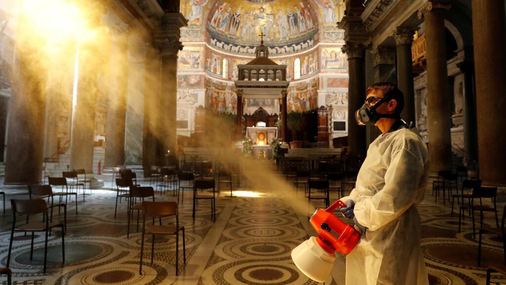 Un hombre desinfecta las superficies para controlar el Covid-19 dentro de la Basílica de Trastevere, en Roma, Italia, el 11 de mayo de 2020.