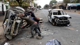 Recolectores de chatarra recuperan una carcasa de un automóvil quemado durante los ataques xenófobos en Johannesburgo, Sudáfrica. 5 de septiembre de 2019.