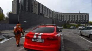 عنصر من قوات الأمن يرشّ مواد معقمة على سيارة أمام مستشفى القديس جاورجيوس في سان بطرسبورغ في روسيا حيث اندلع حريق وأسفر عن ضحايا في 12 أيار/مايو 2020