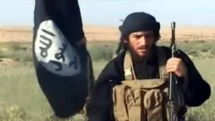 Cette image tirée d'une vidéo de propagande de l'EI mise en ligne sur YouTube le 8 juillet 2012 montre Abou Mohamed al-Adnani parlant au côté du drapeau de l'organisation jihadiste.