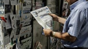 A man reads the headlines of the first issue of Nidaa Al-Watan, a new daily newspaper published in Lebanon, in the capital Beirut