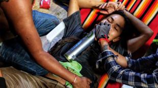 معالجة احد المصابين خلال تظاهرة في تونغيي في بورما في 28 آذار/مارس 2021.