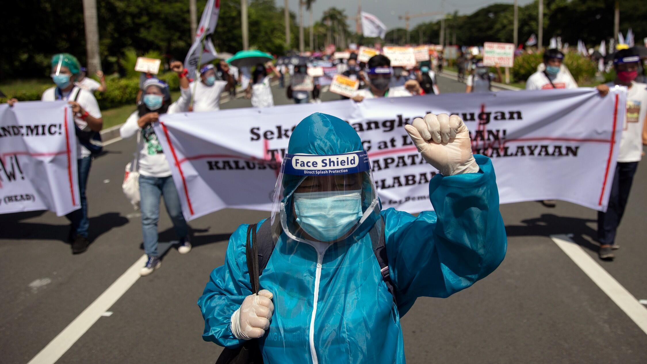 Un trabajador de la salud en traje de materiales peligrosos se une a la protesta antes del quinto discurso del Estado de la Nación del presidente filipino Rodrigo Duterte, en University Avenue, Quezon City, Metro Manila, Filipinas, 27 de julio de 2020.