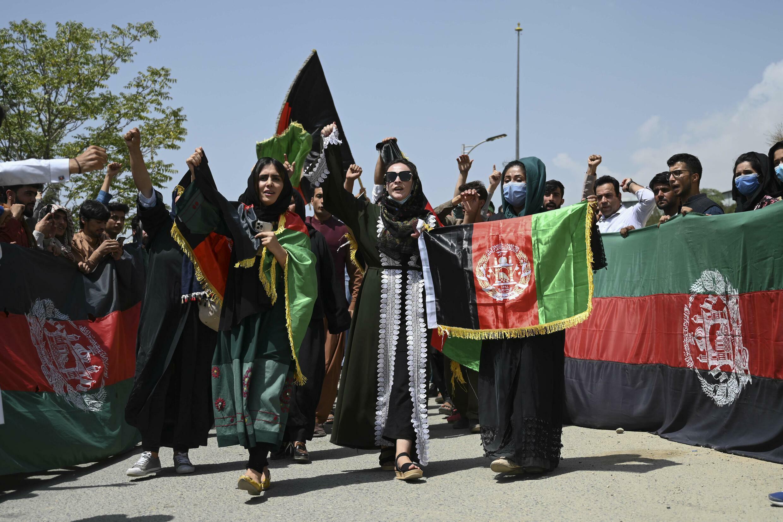 Les Afghans brandissent des drapeaux nationaux tricolores alors qu'ils célèbrent le jour de l'indépendance à Kaboul, quelques jours après la prise du pouvoir par les talibans