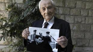 غابرييل باخ (93 عاما) نائب مدعي عام سابق في إسرائيل أشرف على التحقيق مع النازي أدولف أيخمان ويحمل صورة له خلال المحاكمة في 1962