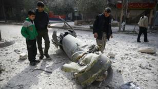 Tres personas inspeccionan los restos de un misil en Douma, Guta Oriental. 23/2/2018