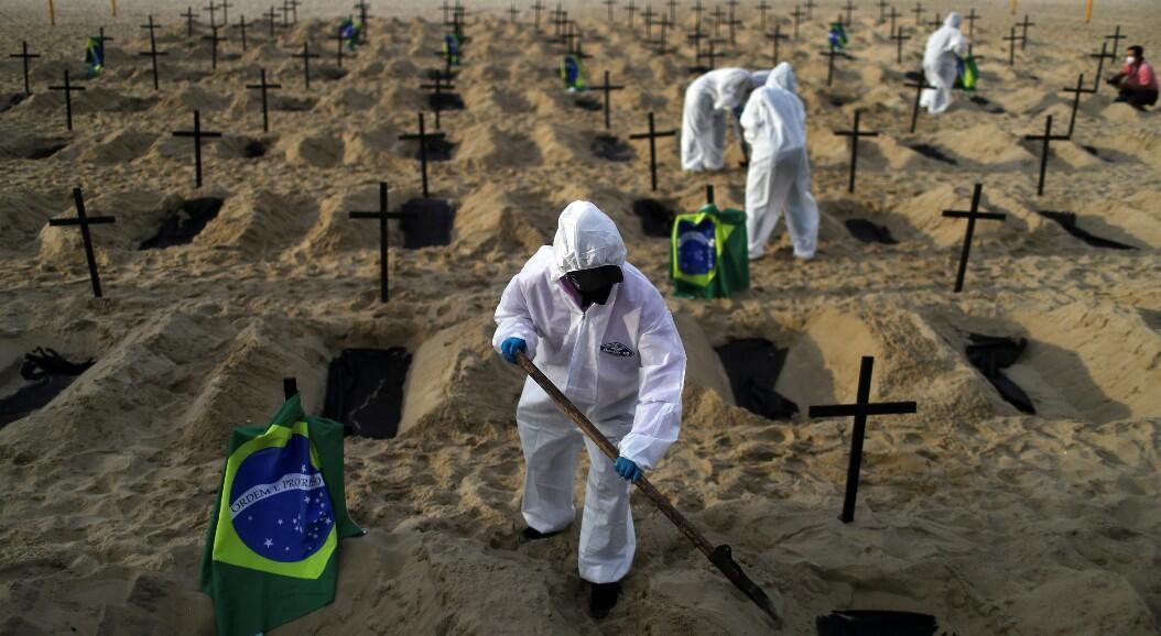 Archivo-Activistas de la ONG Río de Paz con equipo de protección cavan tumbas en la playa de Copacabana para simbolizar a los muertos por el virus del Covid-19, en Río de Janeiro, Brasil, el 11 de junio de 2020.