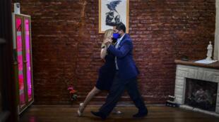 Verónica Pascual (izq.) y Sergio Saucet bailan tango en su casa en Buenos Aires, donde se organiza el Mundial de Tango en modalidad virtual