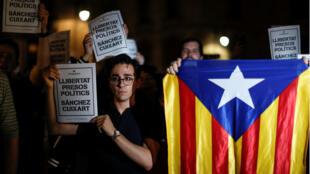 """Manifestantes catalanes sostienen carteles que piden la """"libertad de los presos políticos, Sànchez y Cuixart"""", después de que la Audiencia los encarcelara.16/10/2017"""