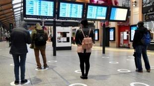 Des passagers à la gare Saint-Lazare à Paris, le 11 mai 2020 respectent les marquages au sol de distanciation sociale