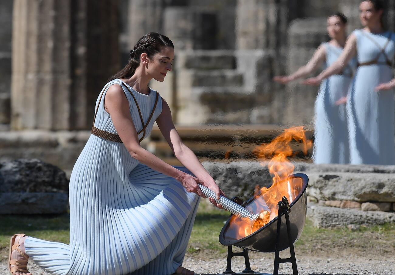 A woman dressed as a priestess lits the Olympic flame during the Olympic ceremony in ancient Olympia, ahead of Tokyo 2020 Olympic Games on March 12, 2020.