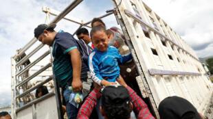 Uno de los niños que viajan dentro de la caravana migrante que partió de Honduras e intenta llegar a Estados Unidos, llora cuando lo bajan de un camión tras finalizar un trayecto del viaje en Chiquimula, Guatemala, el 16 de octubre de 2018.