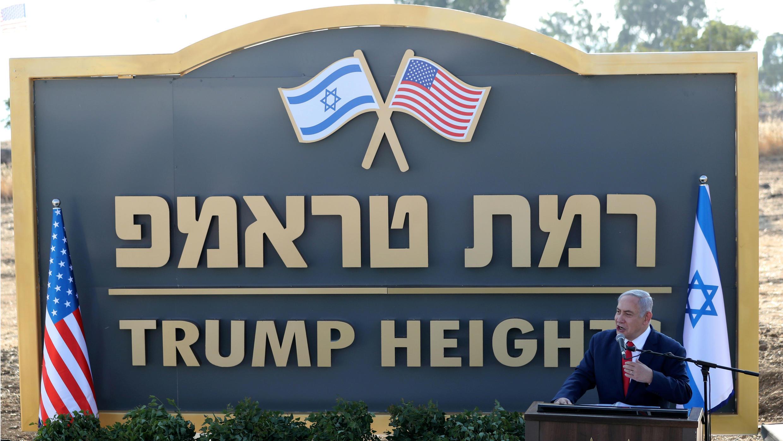 El primer ministro israelí, Benjamin Netanyahu, revela el cartel escrito en inglés y hebrero, de una nueva comunidad que lleva el nombre del presidente estadounidense, Donald Trump, en los Altos del Golán ocupados por Israel, el 16 de junio de 2019.