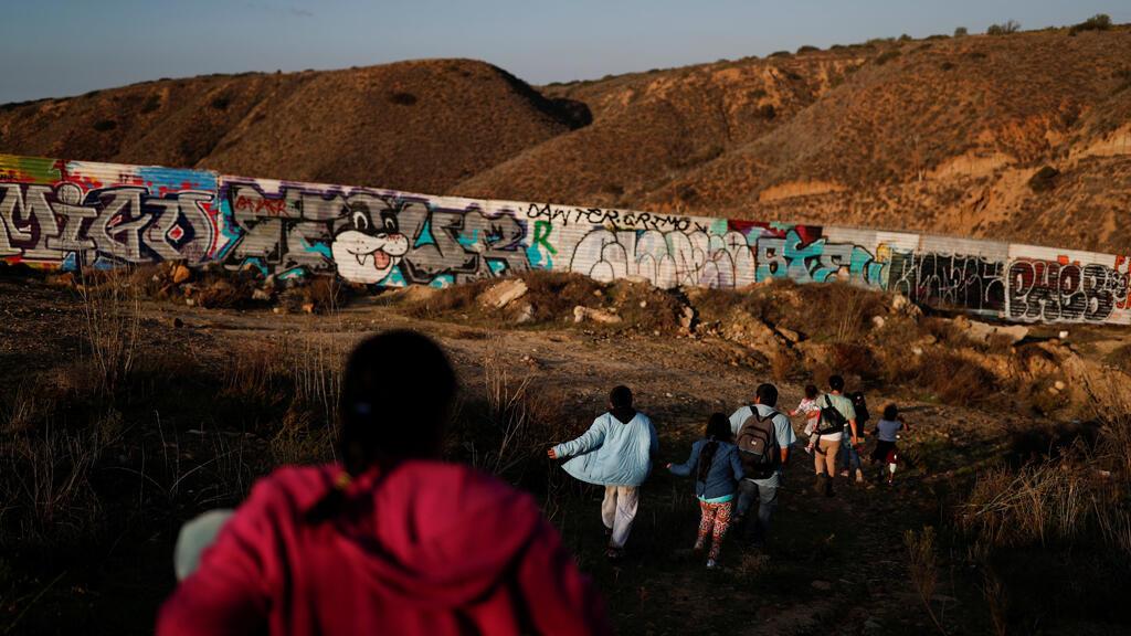 Migrantes, parte de una caravana de miles de habitantes de Centroamérica que intentan llegar a Estados Unidos, caminan junto al muro fronterizo mientras intentan cruzar de México a EE.UU. el 11 de diciembre de 2018.