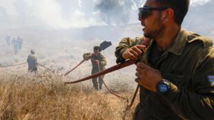 عسكريون إسرائيليون بحاولون إطفاء حريق اندلع في حقل في جنوب إسرائيل قرب الحدود مع قطاع غزة في 23 آب/اغسطس 2020