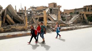 Des écoliers photographiés dans une rue dévastée de Raqqa, le 14 octobre 2018.