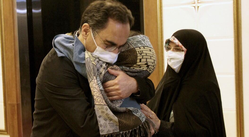 Sirous Asgari, un profesor iraní que fue absuelto en Estados Unidos, tras ser acusado de robar secretos comerciales, abraza a su familia a su llegada al aeropuerto iraní Imam Khomeini, en Teherán, Irán, el 3 de junio de 2020.