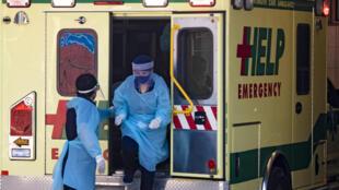 Des personnels soignants sortent d'une ambulance devant un hôpital de Santiago, le 15 mai 2020 au Chili