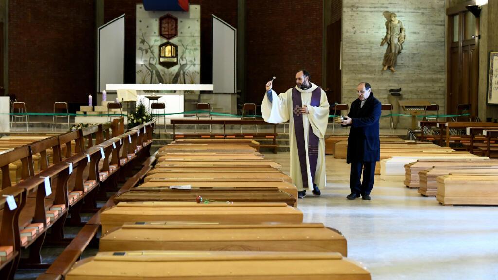 Un cura bendice ataúdes de víctimas del coronavirus en una iglesia de Seriate, Italia, el 28 de marzo de 2020.