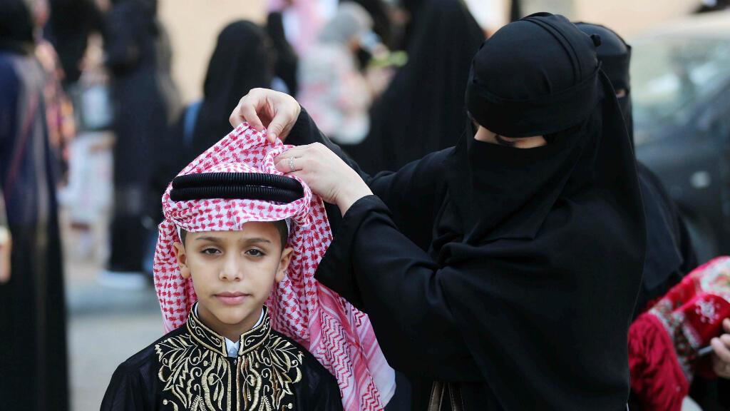 Una mujer coloca la indumentaria de un niño durante la jornada de celebración del Eid al Fitr, la festividad que marca el final del Ramadán, este martes 4 de junio de 2019 en Riad, Arabia Saudita.
