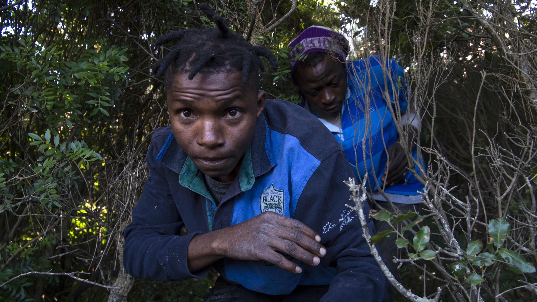 Aboubakar y un compañero migrante caminan en el bosque el 5 de julio de 2018, cerca de la valla que separa Fnideq y el enclave de Ceuta en Marruecos, en el norte de África.