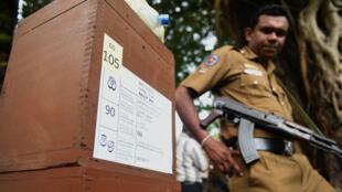 Un policier sri lankais se tient à côté d'un urne à Colombo, le 16 août 2015.