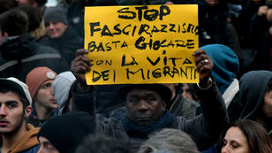 """Un manifestant tient une pancarte clamant """"Stop au fascisme et au racisme, arrêtez de jouer avec la vie des migrants"""" durant une manifestation à Macerata, en Italie, le 10 février 2018."""