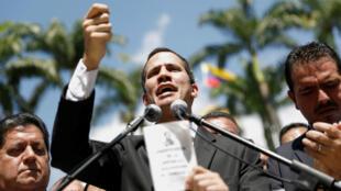 Juan Guaidó, presidente de la Asamblea Nacional de Venezuela, sostiene una copia de la Constitución mientras habla en una conferencia de prensa en Caracas, Venezuela, 21 de enero de 2019.