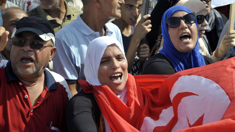 Manifestantes sostienen pancartas en la Plaza del Bardo, Túnez, el 11 de agosto de 2018.