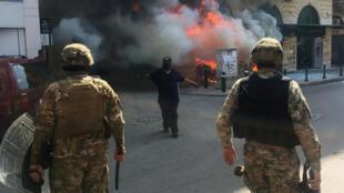 Un manifestante cerca de un banco en llamas en Trípoli se enfrenta a los soldados el 28 de abril de 2020.