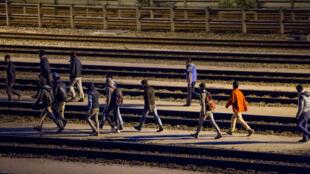 Des migrants s'apprêtent à forcer l'entrée sur le site d'Eurotunnel, dans la nuit du 27 au 28 juillet 2015