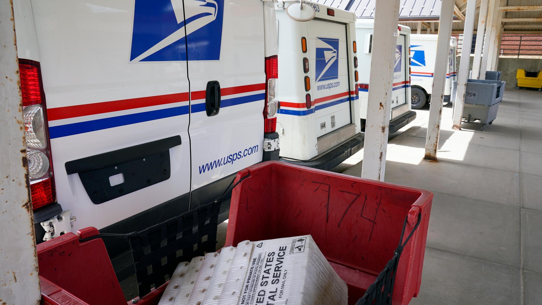 Los vehículos de entrega de correo están estacionados afuera de una oficina de correos en Boys Town, Nebraska, el martes 18 de agosto de 2020.