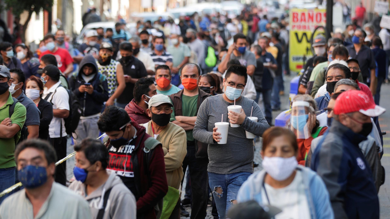La gente espera en la fila a lo largo de la calle antes de ingresar al área donde están abiertas las tiendas, durante la reapertura gradual de las actividades comerciales en la ciudad, a medida que continúa el brote de la enfermedad por coronavirus (COVID-19), en la Ciudad de México, México, 14 de julio de 2020.