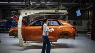 Una empleada con mascarilla pasa frente a la carrocería de un automóvil en la cadena de montaje de la fábrica de Volkswagen en la localidad portuguesa de Palmela, 30 km al sur de Lisboa, el 13 de mayo de 2020