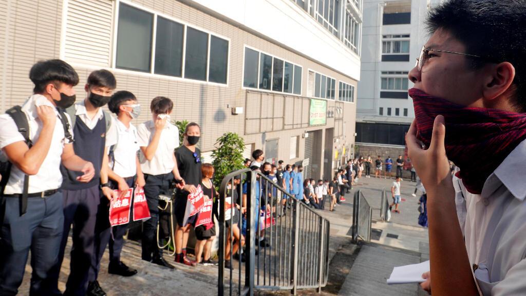 Estudiantes de secundaria gritan consignas mientras forman una cadena humana en Hong Kong.