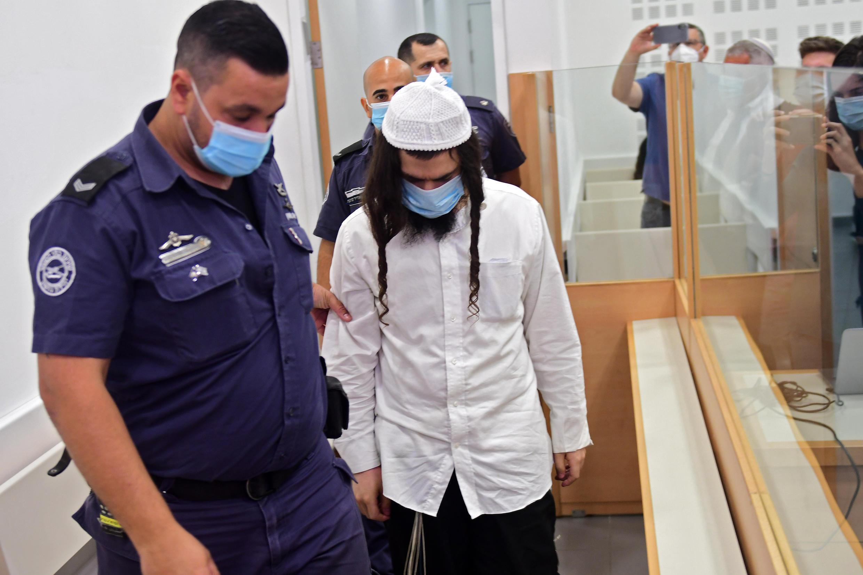 Amiram Ben-Ouliel, un colon juif, est conduit par des policiers au tribunal de district de Central Lod, dans le centre d'Israël, le 18 mai 2020.