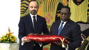 Le président sénégalais Macky Sall reçoit le sabre El Hadj Oumar Tall des mains d'Edouard Philippe, au palais présidentiel à Dakar, le 17 novembre 2019.