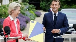El presidente francés Emmanuel Macron (derecha) y la presidenta de la Comisión Europea, Ursula Von der Leyen, posan con una carpeta durante una conferencia de prensa al margen de su reunión para anunciar la luz verde al plan de recuperación francés posCovid-19 en París, el 23 de junio de 2021.