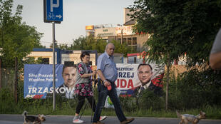 People walk their dogs and pass by campaign posters of Polish President Andrzej Duda (R) and Warsaw Mayor Rafal Trzaskowski in a suburb of Warsaw on June 25, 2020.