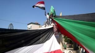 فلسطينيون فرحون بالإعلان عن اتفاق مصالحة بين فتح وحماس يحتفلون بشوارع غزة وهم يحملون علمين عملاقين لفلسطين ومصر 12 أكتوبر 2017