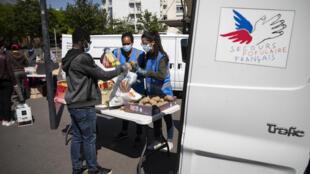 Des bénévoles du Secours populaire distribuent des produits alimentaires et des soins d'hygiène aux étudiants devant l'université Paris8, à Saint-Denis, près de Paris, le 6mai2020.