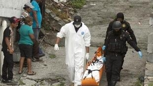 Policemen and forensic personel carry one of four bodies, three women and one man, from a crime scene in Monterrey.