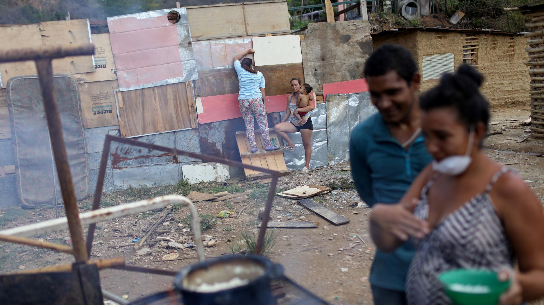 La gente cocina con leña mientras una mujer trabaja en una casa hecha con barro, palos y hojalata en el municipio de Sucre, cerca de Caracas, Venezuela. Foto tomada el 12 de junio de 2020.