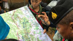 Soldados leen un mapa cerca de las cuevas de Tham Luang durante una búsqueda de 12 miembros de un equipo de fútbol infantil y su entrenador, en Chiang Rai.