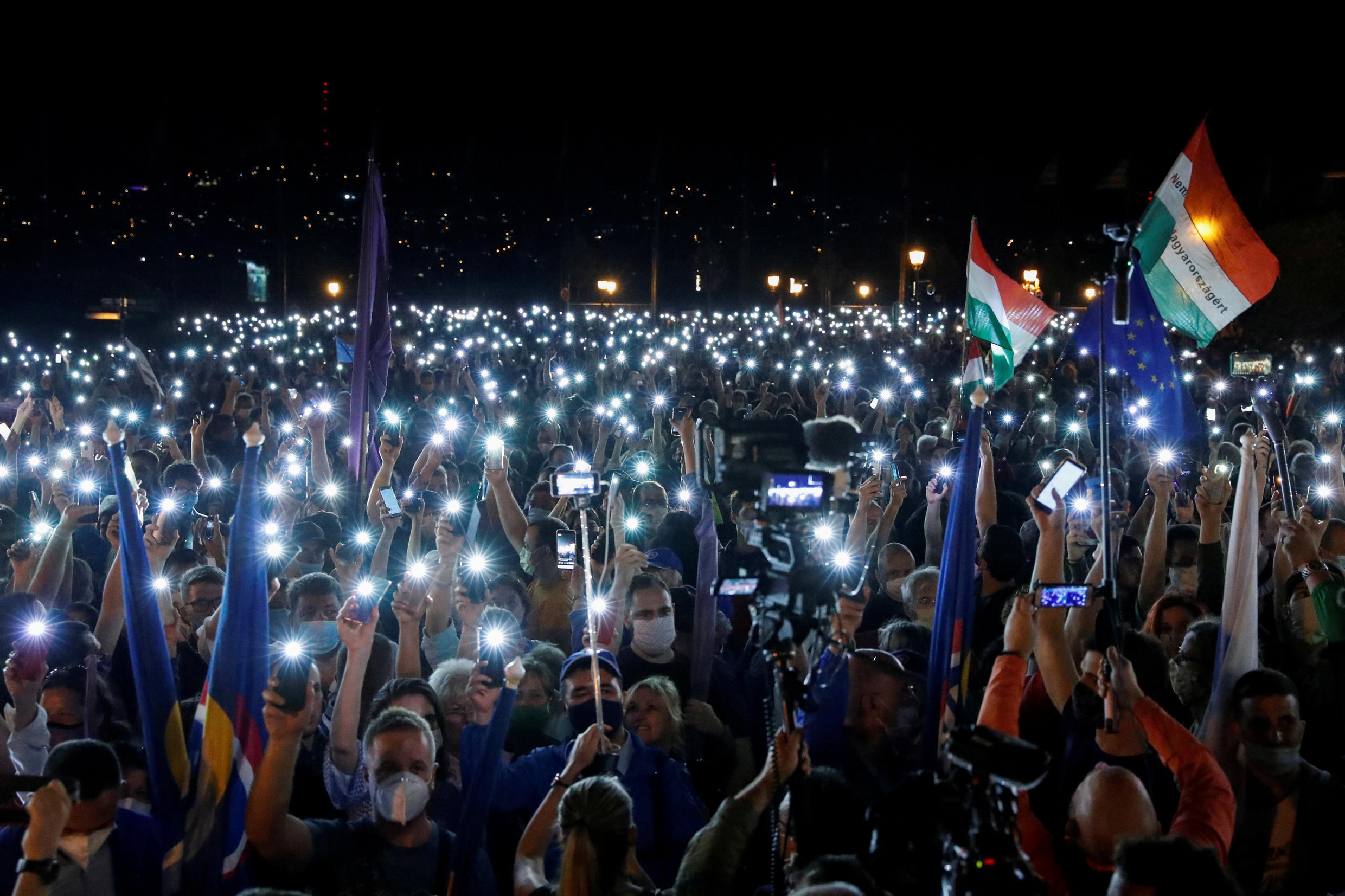 People light up their cell phones as they take part in a protest for media freedom after the editor-in-chief of Index, Hungary's leading independent news website was fired, near the Sandor Palace, in Budapest, Hungary, July 24, 2020.